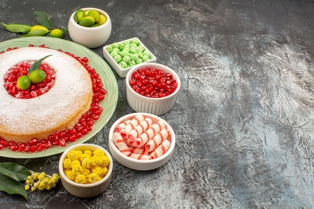 Vista ravvicinata laterale dolci ciotole di caramelle dolci gialli verdi melograno una torta sul piatto