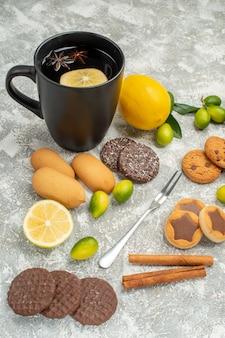 Vista ravvicinata laterale dolci una tazza di tè forchetta gli appetitosi biscotti agli agrumi