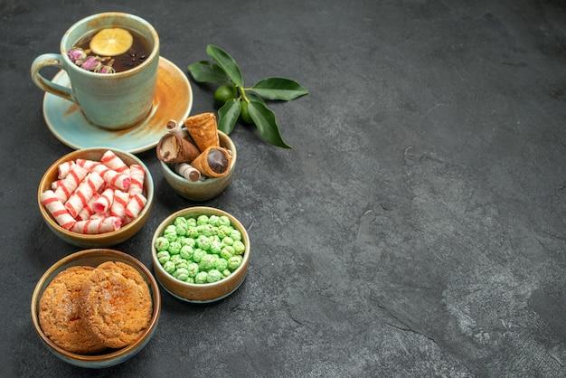 Vista ravvicinata laterale dolci una tazza di tè con limone, agrumi, biscotti, cialde, caramelle