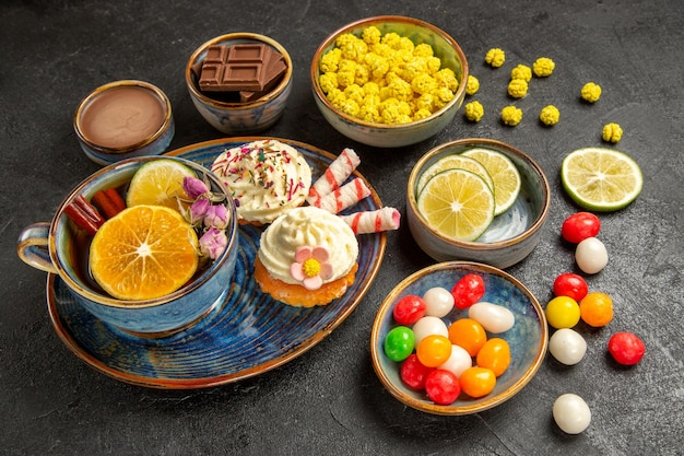 Side close-up view sweets on the table the appetizing cupcakes a cup of herbal tea and bowls of chocolate limes colorful sweets and chocolate cream on the table