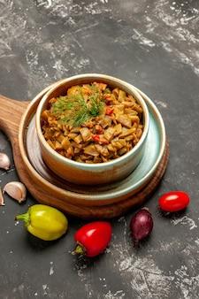 어두운 탁자에 있는 나무 판자에 있는 맛있는 요리 맛있는 요리 피망 양파 토마토를 가까이에서 볼 수 있습니다.