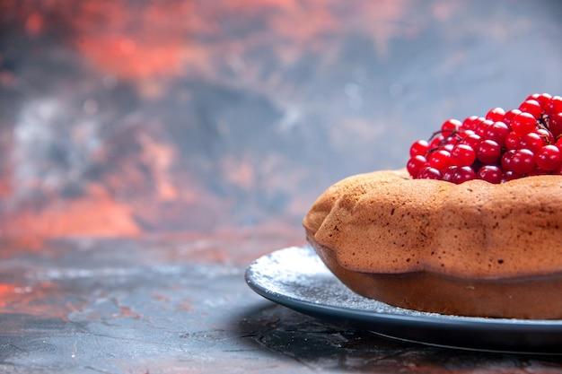 Vista ravvicinata laterale gustoso piatto grigio di torta e ribes rosso sullo sfondo rosso-blu
