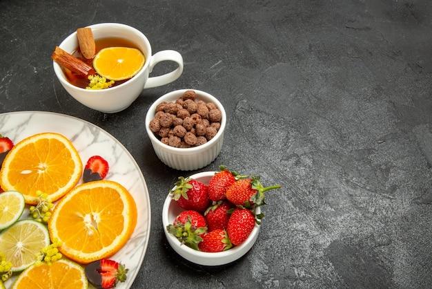 Vista ravvicinata laterale tè e frutta piatto di pezzi di limone arancia fragole ricoperte di cioccolato una tazza di tè e ciotole di nocciole e fragole sul lato destro del tavolo