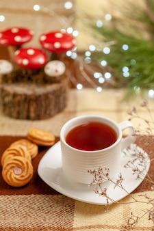 Vista ravvicinata laterale teiera biscotti appetitosi e una tazza di tè su un piattino accanto alla teiera e ai rami degli alberi sulla tovaglia a scacchi