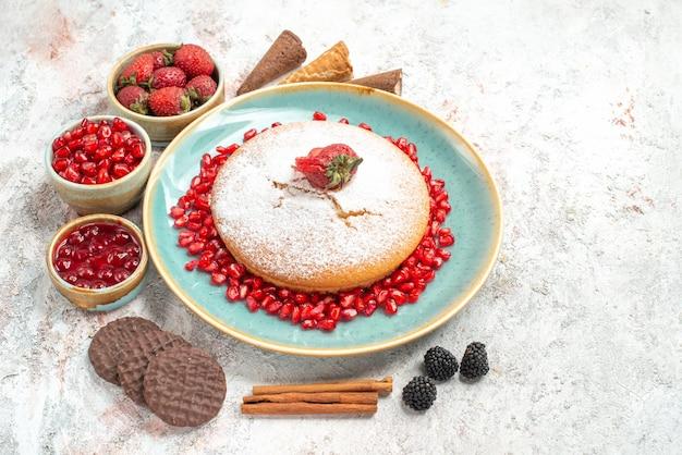 側面のクローズアップは、ボウルの横にザクロのクッキーが付いているケーキシナモンスティックケーキを表示します