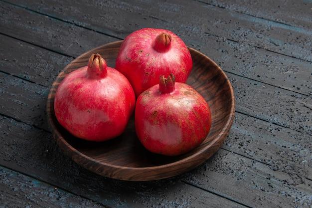 테이블에 석류의 측면 클로즈업 보기 세 석류 갈색 그릇