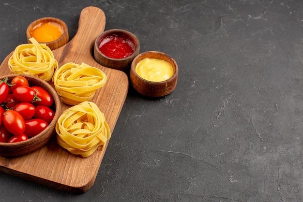 テーブルの上のキッチンボード上のトマトとパスタのボウルの横にあるソースの側面のクローズアップビュートマトとパスタのボウル