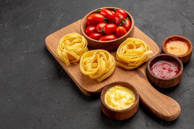 Вид сбоку крупным планом помидоры и макароны разделочная доска с миской помидоров и макаронных изделий на ней между мисками разных соусов на столе