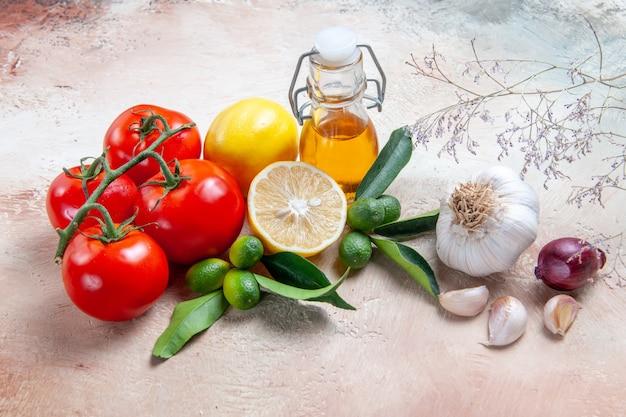 Vista ravvicinata laterale pomodori bottiglia di olio aglio pomodori con pedicelli agrumi