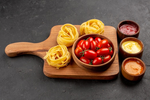 Side close-up view tomatoes and pasta bowls of different sauces next to the bowl of appetizing tomatoes and pasta on the kitchen board on the table