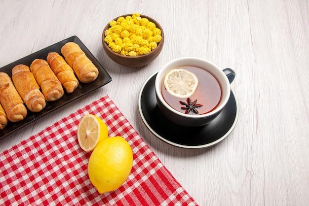 黄色いキャンディーのボウルと白いテーブルの上のお茶の横にあるペストリーの市松模様のテーブルクロスの暗いプレート上の側面のクローズアップビュー管状ペストリーレモン