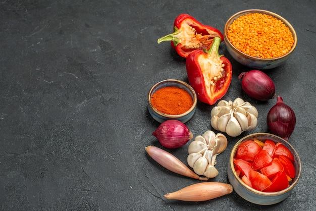 블랙 테이블에 렌즈 콩 피망 토마토 향신료의 측면 확대보기 야채 그릇