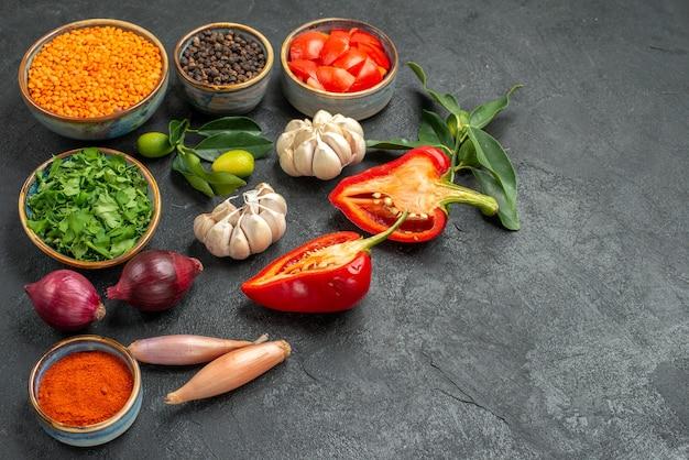 렌즈 콩 마늘 허브 양파 향신료 토마토 피망의 측면 확대보기 야채 그릇