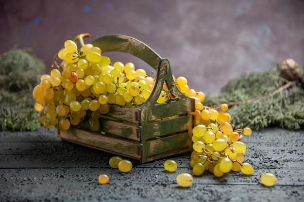 側面のクローズアップビュートウヒの枝の横にある灰色のテーブルの上の木製の箱に白ブドウの束を食欲をそそる白ブドウ