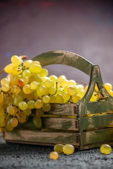 Vista ravvicinata laterale grappolo di uva bianca in scatola di legno su tavolo scuro accanto a rami di abete rosso