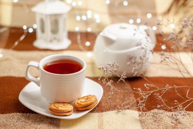찻주전자와 나뭇가지 옆에 쿠키가 있는 컵에 쿠키 홍차가 있는 차 한 잔을 가까이서 봅니다.