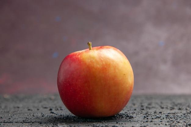 Vista laterale ravvicinata mela mela gialla-rossastra su un tavolo grigio