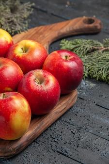 나무 가지 사이의 회색 배경에 있는 커팅 보드에 있는 측면 닫기 사과와 가지 노란색-빨간 사과