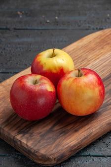 Вид сбоку крупным планом фрукты на разделочной доске одно красное яблоко и два желто-красных яблока на коричневой разделочной доске на сером столе