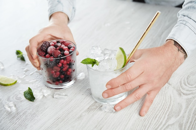 Side close view man hands hold glasses with frozen berries and ice cubes with lime