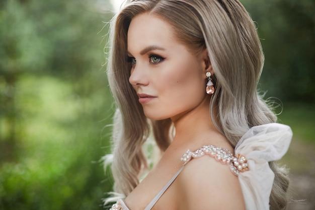 Вид сбоку платиновой блондинки, красивой женщины в свадебном платье и с дорогими роскошными серьгами с бриллиантами