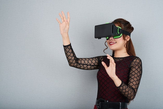Side cropped view of young woman in vr headset gesturing