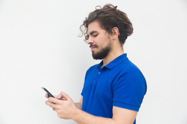 Side of focused guy texting message on smartphone