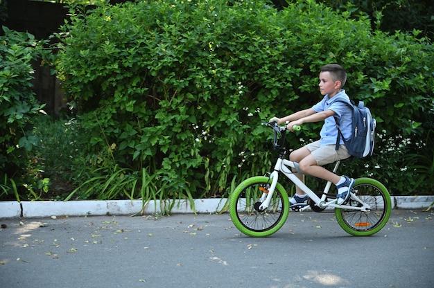 早朝のアスファルト道路で自転車に乗った小学生の横長の肖像画。街で自転車に乗っている少年