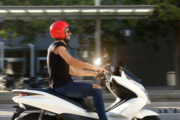 Side of handsome smiling man on motorcycle ride in city