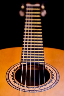 On the side lies a wooden acoustic guitar close-up. perspective frame with highly blurred background