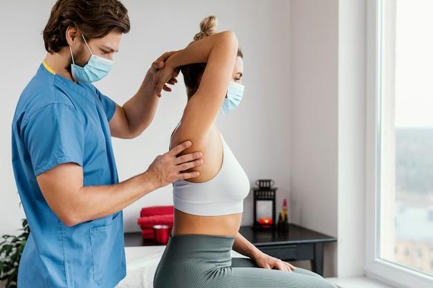 Lato del terapista osteopatico maschio con mascherina medica che controlla l'articolazione della spalla del paziente femminile