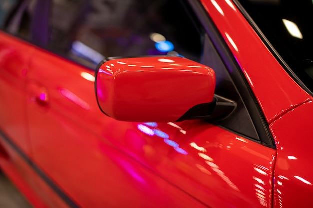The side mirror of a red sports car. rear-view mirror.