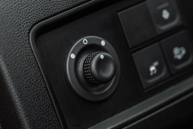 Панель управления боковыми зеркалами на боковой двери. водитель автомобиля регулирует контроллер бокового зеркала. кнопка управления боковыми зеркалами для регулировки боковых зеркал.