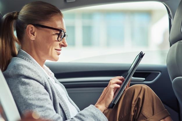 디지털 태블릿을 사용 하여 안경을 쓰고 성공적인 웃는 비즈니스 여자의 측면은 차, 출장에 뒷좌석에 앉아있는 동안 작동합니다. 운송 및 차량 개념