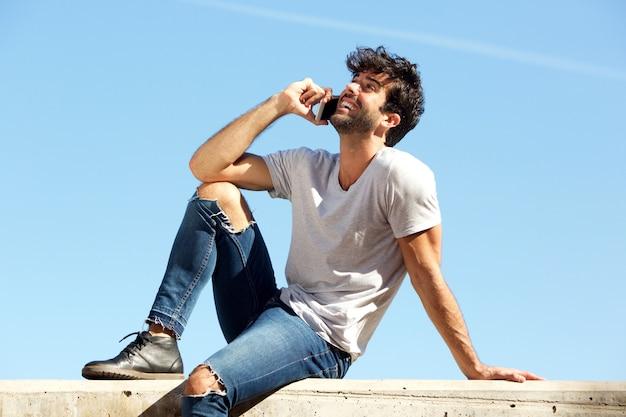 スマートフォンで話すコンクリートの壁に座っている幸せな男の側