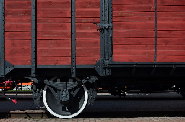 The side of the old brown wooden freight car with the wheel