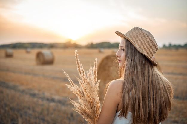 わら俵がたくさんある収穫された畑でドライフラワーの花束を持った10代の少女のサイド写真