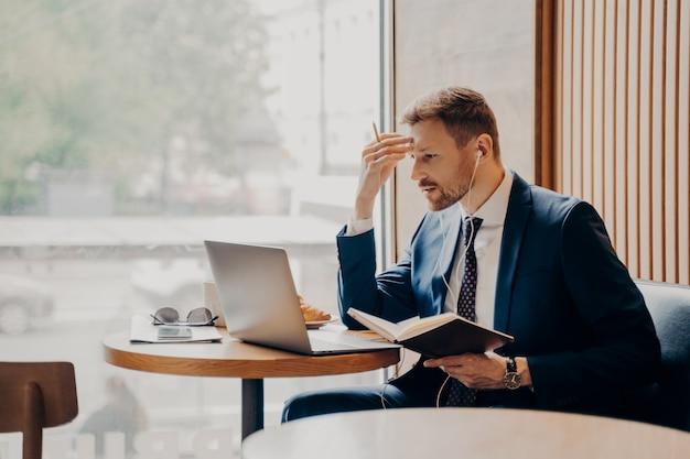 Боковое фото успешного мужского сотрудника компании в наушниках, работающего онлайн из кафе, смотрящего бизнес-видео на портативном компьютере, сидя рядом с большим ярким окном в строгом стильном костюме