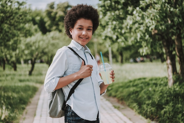 Side photo of smiling boy holding juice in park.