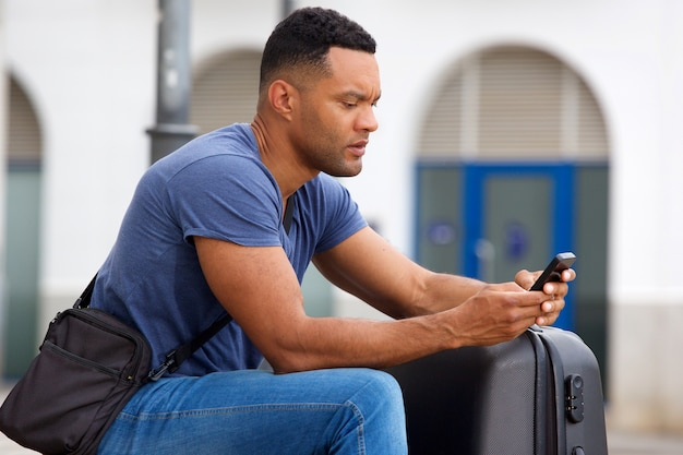 Side portrait of african man sitting outside with suitcase and using cell phone