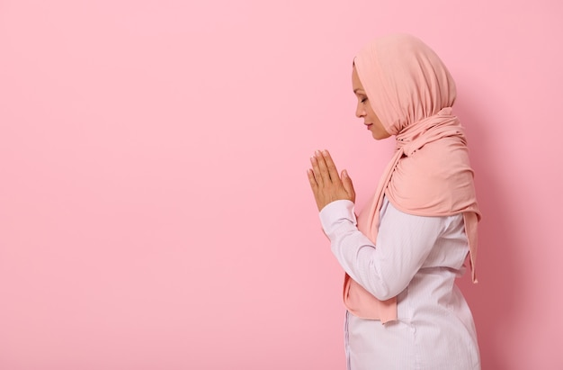 Side portrait of a beautiful and serene muslim arab woman in pink hijab and strict outfit with palms folded together at face level performing namaz, isolated on colored background with space for text