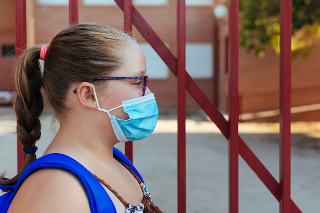 Side portrait of a blonde girl with a blue backpack and a face mask. back to school.
