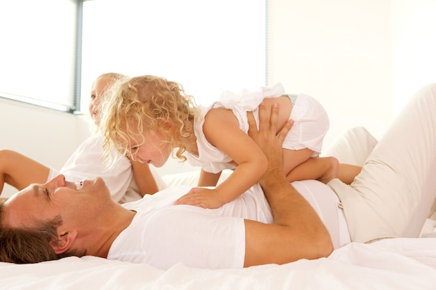 Side portrait of loving young family playing on bed at home