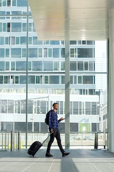 Side portrait of man walking with suitcase and smart phone