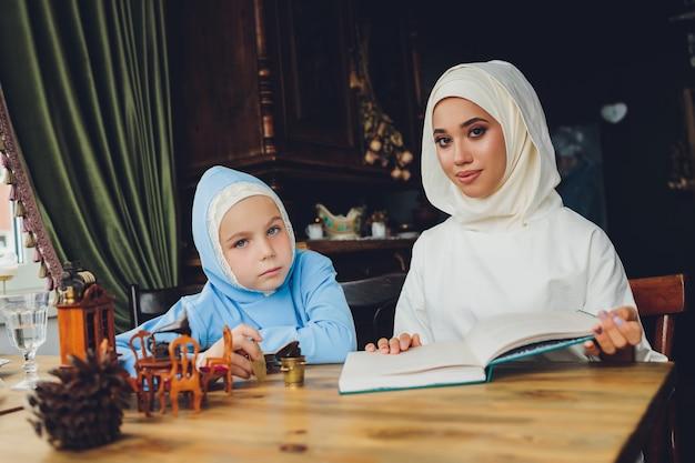 青いヒジャーブを身に着けている小さなイスラム教徒の少女の側面の肖像画