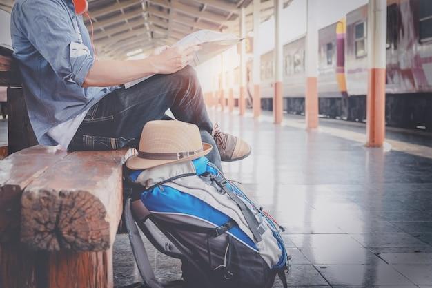 マップと一緒に座っている若い男性の旅行者の横の肖像画は、旅行する場所と列車を待っている鞄を選び、ヴィンテージトーンフィルターが効きました。