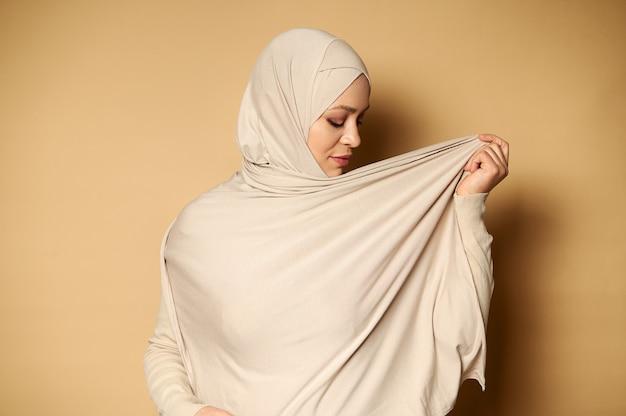 ヒジャーブを身に着けているエレガントな若いイスラム教徒の女性の側面の肖像画