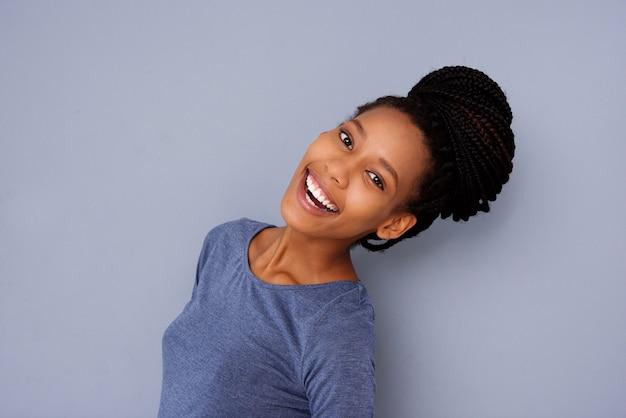 灰色の背景に笑いを編んだ髪のパンを持つ美しい少女の側の肖像画