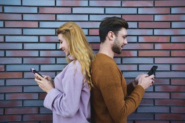 美しい若いカップルの横向きの肖像画は、スマートフォンを使用して、茶色のレンガの壁に背中合わせに立って笑っています。