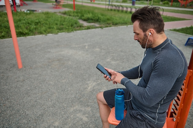 이어폰을 끼고 휴대전화를 들고 카피 공간이 있는 검은색 빈 화면에 손가락을 대고 있는 유럽 스포츠맨의 측면 초상화. 심장 박동을 확인하는 모바일 애플리케이션에서 운동하는 선수
